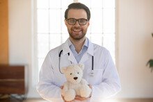 Portrait Of Smiling Young Caucasian Male Pediatrician In White Medical Uniform Hold Fluffy Teddy Bear Toy Show Care And Good Service In Children Hospital. Happy Man Doctor Work In Kids Private Clinic.