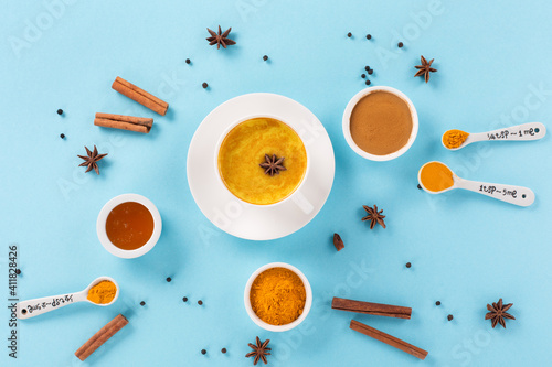 Turmeric golden milk latte with spices, cinnamon and honey on blue background Wallpaper Mural