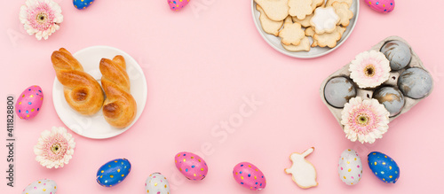 Obraz Homemade Easter bunny buns, sugar cookies, chocolate eggs, flowers on pastel pink background. Festive Easter breakfast concept. - fototapety do salonu