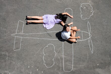 Girls Playing In A Chalk Airplane