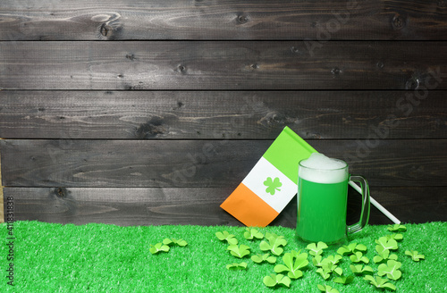 Mug of green beer and flag of Ireland on green grass with clover leaves on dark wooden planks background. Saint Patricks Day banner, poster, flyer, invitation template