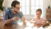 Caring Young Caucasian Father And Little Daughter Engaged In Funny Game String Colorful Beads On Thread. Loving Happy Dad Have Fun Play Make Bracelets With Cute Small Girl Child. Hobby Concept.