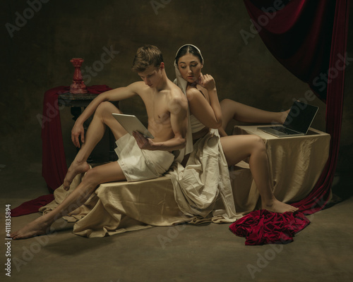 Peeking of what man do. Modern remake of classical artwork with modern tech theme - young medieval couple on dark background, golden colored. Concept of technologies, devices, communication, ad.