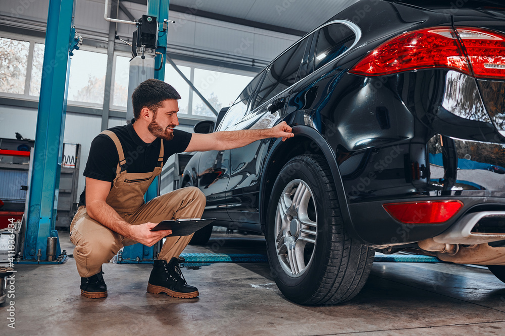 Fototapeta Handsome mechanic in uniform is making notes examining car in auto service.