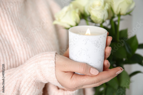 Woman holding burning candle with wooden wick, closeup © New Africa