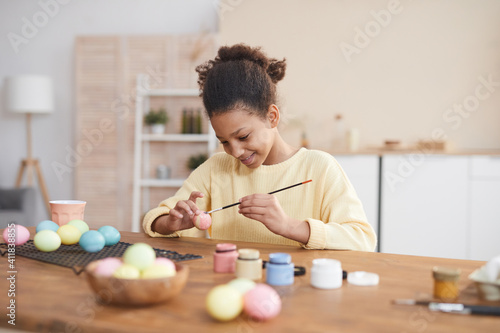 Obraz Minimal portrait of smiling African-American girl hand painting Easter eggs with pastel colors while enjoying DIY decorating at home, copy space - fototapety do salonu