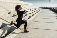 Outdoor Workout Concept. Fit Slim Woman With Curly Hair Stretches Or Warms Up On An Urban Embankment With Concrete Slabs