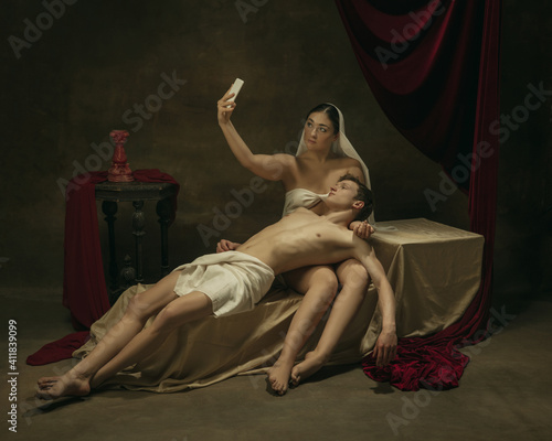 Take selfie for social. Modern remake of classical artwork with modern tech theme - young medieval couple on dark background, golden colored. Concept of technologies, devices, communication, ad. © master1305