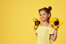 Happy Little Child Girl In T-shirt Holding Yellow Longboard On Shoulders Over Yellow Background