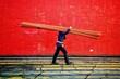 Leinwandbild Motiv Side View Of Man Carrying Metallic Rods While Walking Against Wall