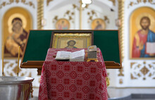 Closeup Interior Of A Christian Church. Prayer Table Covered With Patterned Red Cloth. A Metal Container With Holy Water For Baptism. Bible, Casket, Icon And Blurred Iconostasis In The Background.