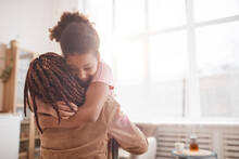 Minimal Waist Up Portrait Of Happy African-American Girl Embracing Mother In Cozy Home Interior Lit By Sunlight, Copy Space