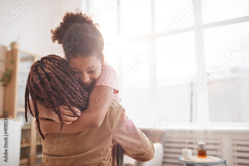 Fototapeta Minimal waist up portrait of happy African-American girl embracing mother in cozy home interior lit by sunlight, copy space obraz