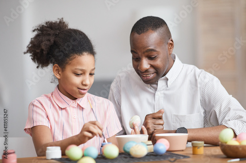Obraz Minimal portrait of young African-American girl painting Easter eggs while enjoying DIY decorating with father - fototapety do salonu