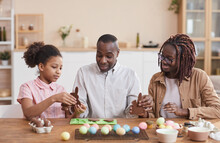 Portrait Of Loving African-American Family Making Chocolate Easter Bunnies While Sitting At Wooden Table In Cozy Home Interior And Enjoying Holiday Preparations