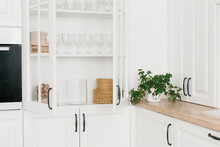 Opened White Glass Cabinet With Clean Dishes And Decor. Scandinavian Style Kitchen Interior. Organization Of Storage In Kitchen.
