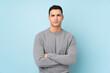 Leinwandbild Motiv Young caucasian handsome man isolated on blue background keeping arms crossed