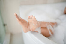 Woman's Feet In The Bath. She Was Taking A Shower With Soap To Cleanse Her Body.