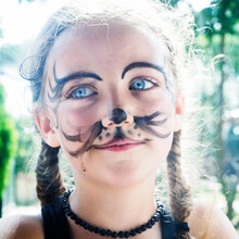 Close-up Portrait Of A Smiling Girl With Tiger Face Paint Standing In A Garden, Italy