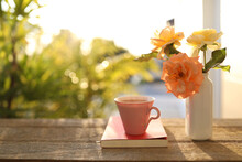 Pink Tea Cup And Roses Flower Vase And Notebook On Wooden Table