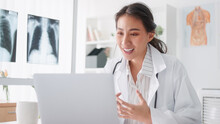 Asian Female Doctor Using Laptop Computer Online Video Call Remote Talking To Patient, Prescribe Medicine. Tele Medical, Telehealth, Hospital Clinic Health Care Service, Or Internet Technology Concept