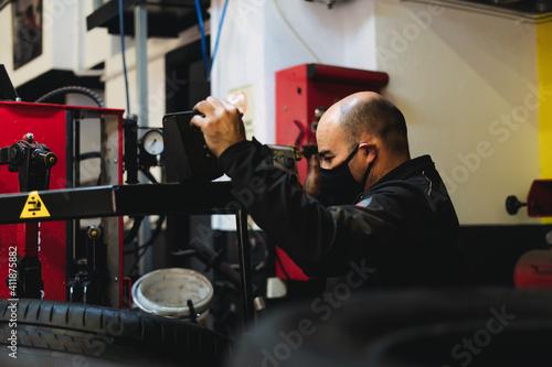 Платно Auto mechanic working in garage. Repair service.