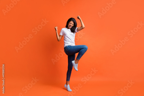 Obraz Full length photo of lady open mouth raise fist knee wear white t-shirt jeans sneakers isolated orange color background - fototapety do salonu