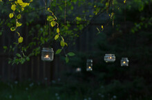 Upcycled Glass Jar Garden Lanterns Illuminated By Candles Hang From Tree Branches In Evening