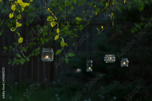 Fotografie, Obraz Upcycled Glass Jar Garden Lanterns Illuminated By Candles Hang From Tree Branche