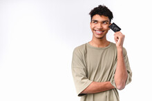 Pensive Young Mixed-race Man Holding Credit Card In Casual Attire Isolated Over White Background