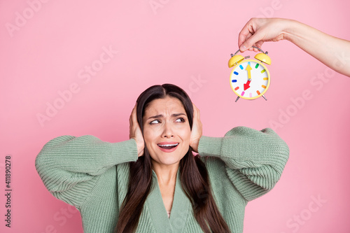 Obraz Photo of girl close ears scared worried look alarm clock wear green cardigan isolated pastel pink color background - fototapety do salonu