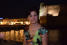 Portrait Of Smiling Beautiful Woman Against Castel Dell Ovo At Night