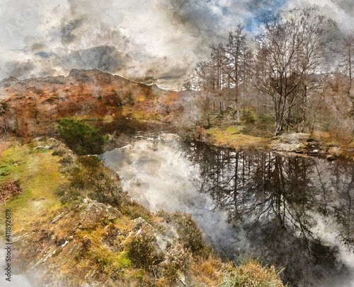 Majestic Winter landscape image view from Holme Fell in Lake District towards snow capped mountain ranges in distance in glorious evening light with Autumnal colors trees © veneratio