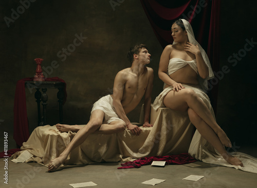 Emotions. Modern remake of classical artwork - young medieval couple on dark background, golden colored. Concept of art, creativity, comparison of eras, history, modernity and renaissance. © master1305