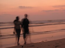 Blurred Motion Of Couple Walking At Beach During Sunset