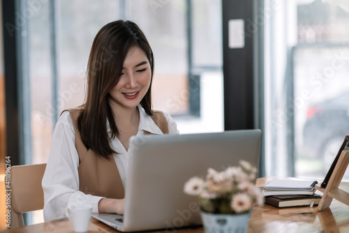 Young Beautiful smiling Asian business woman holding a coffee and laptop Placed at the wooden table at the office