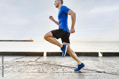 man runner running in morning light of dawn along sea embankment Fototapet