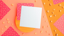 Abstract Flatlay Square Note Sheets On Round Wooden Base,yellow Beige Diagonal Paper Background,corners Of Pink Paper With White Polka Dots Around Perimeter,scattered Pebbles.Design Pattern Copy Space