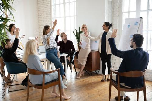 Fotografía Motivated employees raising hands, asking coach at training