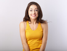 Beautiful Happy Toothy Chuckling  Woman With Brown Hair In Casual Yellow T-shirt Looking Happy On Grey Background With Empty Copy Space.