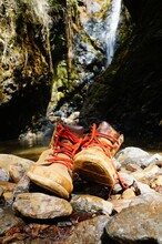 Brown Boots With Red Laces On Rocks By The Water In Beautiful Caves