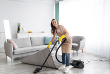 Positive Female Housekeeper Using Vacuum Cleaner To Tidy Modern Apartment. Sanitary Service Concept