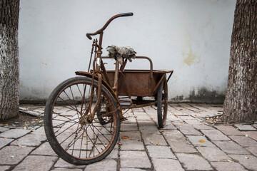 Fototapeta na wymiar Rusty Bicycle On Footpath Against Wall