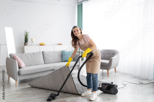 Positive female housekeeper using vacuum cleaner to tidy modern apartment Wallpaper Mural