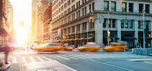 New York City - Busy Intersection With Yellow Taxis Speeding Through The Crowded Intersection Of 5th Avenue And 23rd Street With The Light Of Sunset In The Background