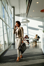 African American Business Woman Using Mobile Phone And Walking In The Office