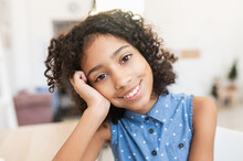 A Close-up Portrait Of Pretty African Preteen Girl, A Schoolgirl Wearing Dot Shirt Looks At Camera Sitting At The Desk At Home