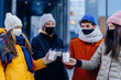 Group of four young people in facial protective masks meeting outdoor in winter day. New normal lifestyle concept with happy guys and girls.