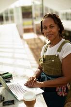 Portrait Confident Female Garden Shop Owner At Laptop In Greenhouse