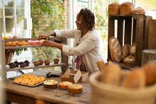 Female Baker Arranging Pastry Display In Shop